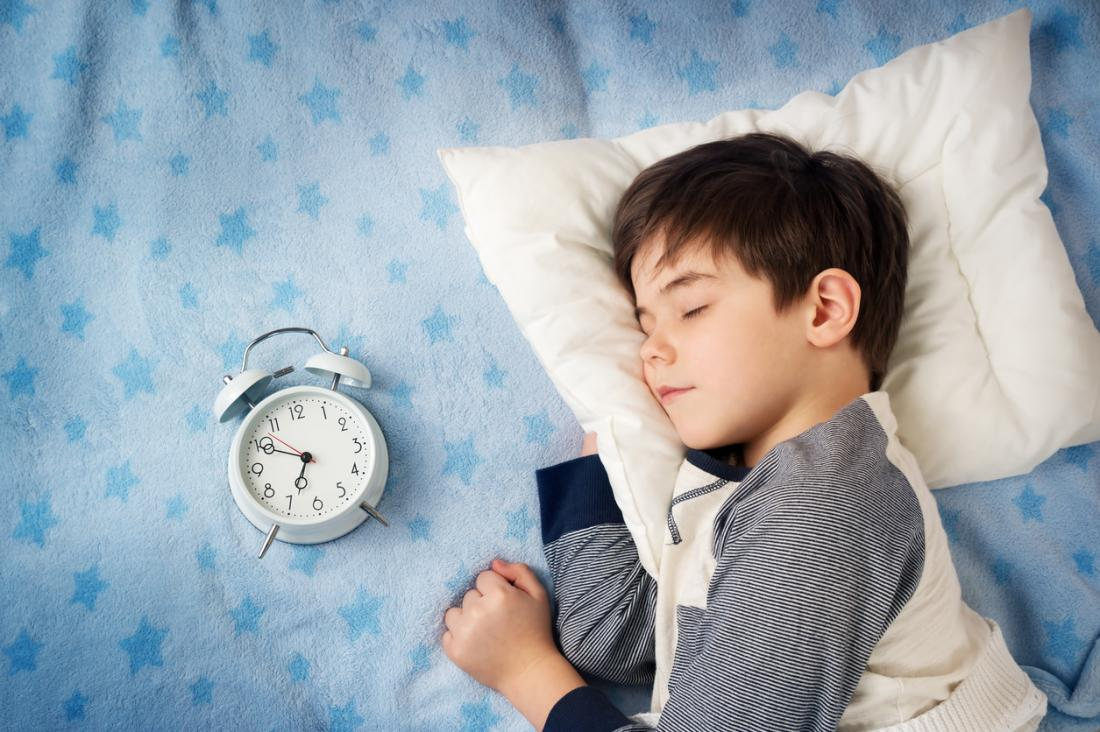 child-sleeping-with-clock